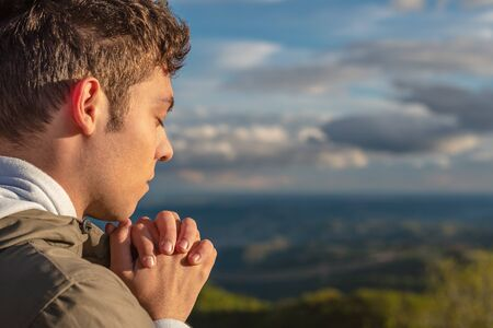 Christian worship and praise. A young man is praying and worshiping in the evening.