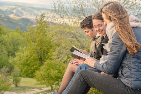 Chrześcijański kult i uwielbienie. Przyjaciele modlący się i czytający Biblię wieczorem.