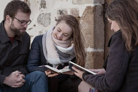 Christian worship and praise. Happy friends reading the bible together in the evening.