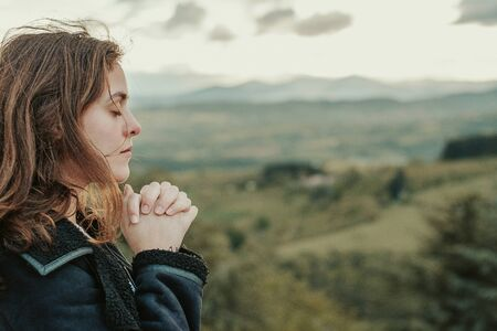 Christian worship and praise. A young woman is praying and worshiping in the evening. Reklamní fotografie