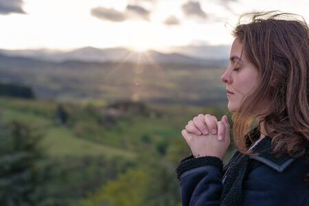 Christian worship and praise. A young woman is praying and worshiping in the evening. Archivio Fotografico