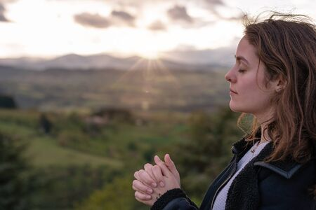 Christian worship and praise. A young woman is praying and worshiping in the evening. Фото со стока