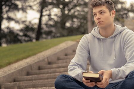 Christian worship and praise. A young man is praying and reading the bible in the evening.