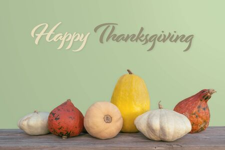 Holidays and season - autumn. Different beautiful colored pumpkins with a flowered background. Text: Happy Thanksgiving
