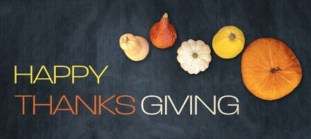 Holidays and season - autumn. Different beautiful colored pumpkins with dark background. Text: Happy Thanksgiving