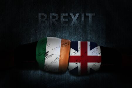 Political relationships. Irish and British Flag on boxing gloves. Partnership and conflicts. Brexit. Stock Photo