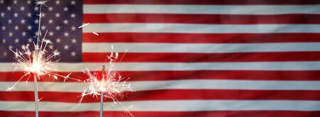 American National Holiday. US Flags with American stars, stripes and national colors. Independence Day. 4th July. Sparkler. Stock Photo