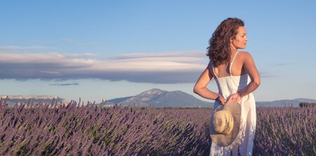 Summertime in lavender. Young beautiful woman in lavender flowers field at sunset in white dress. Provence. France.