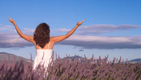 Christian worship and praise. A young woman is praying and worshiping in the evening. Worship and prayer banner. Lavender field.