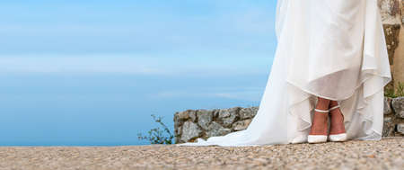 Wedding dress. Woman in wedding dress with white shoes outdoors. Panorama.