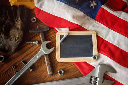 American National Holiday. US Flags with American stars, stripes and national colors. Construction and manufacturing tools on wooden background. Labor day background concept. 免版税图像
