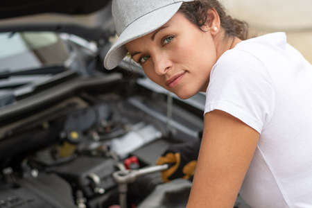Woman work power. Female auto mechanic worker on car engine using a ratchet. Repair service. Authentic close-up shot. Labor day.