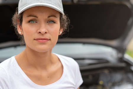 Woman work power. Female auto mechanic worker standing in front of car engine. Repair service. Authentic close-up shot. Labor day.