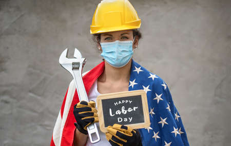 American National Holiday. US Flags with American stars, stripes and national colors. Portrait of female worker with face. Authentic close-up shot. Labor day. 免版税图像