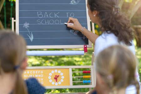 Back to School. Back to School written on classroom chalkboard by teacher. Outdoor classroom.