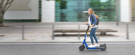 Urban city lifestyle. Young beautiful woman riding an electric scooter in downtown district. Modern urban background.