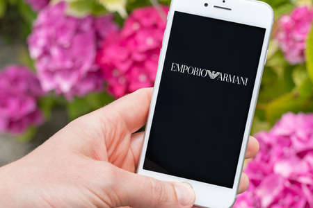 Guilherand-Granges, France - October 07, 2020. Person holding smartphone with Emporio Armani logo. Emporio Armani is an Italian fashion house and luxury goods company.