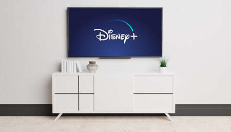 Guilherand-Granges, France - November 10, 2020. Living room and television with Disney Plus logo. American subscription video on-demand over-the-top streaming service.