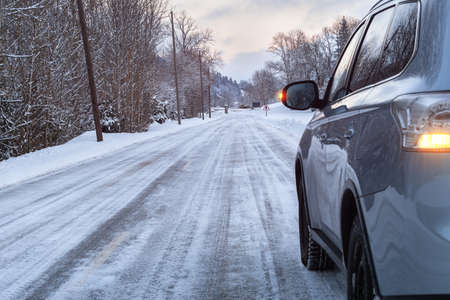 Closeup of car in winter landscape. Road covered with snow. Car tires on snowy road. Winter concept.