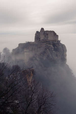 French winter landscapes. Stunning panoramic view of castle ruins Crussol. Foggy mountain landscape. Sea of clouds.