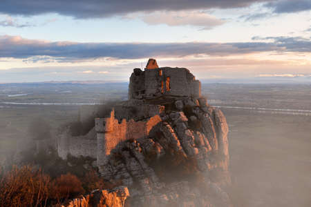French winter landscapes. Stunning panoramic view of castle ruins Crussol. Foggy mountain landscape at sunrise.