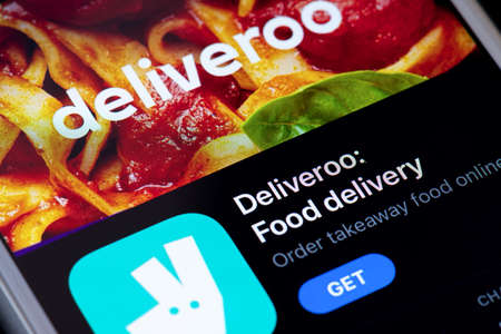 Guilherand-Granges, France - February 08, 2021. Smartphone with Deliveroo app logo. An online food delivery company. 新聞圖片