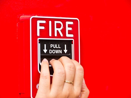 Hand on fire alarm box photo