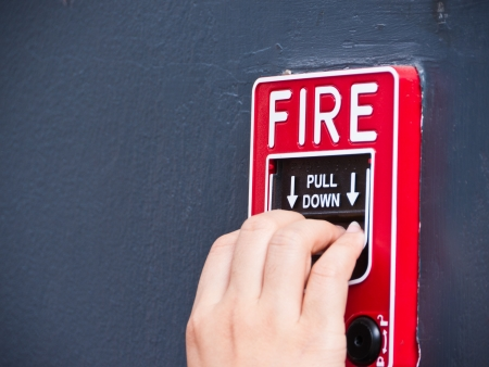 Hand on fire alarm box
