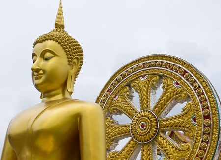 Buddha statue and wheel of the law or wheel of life symbol in Buddhism way