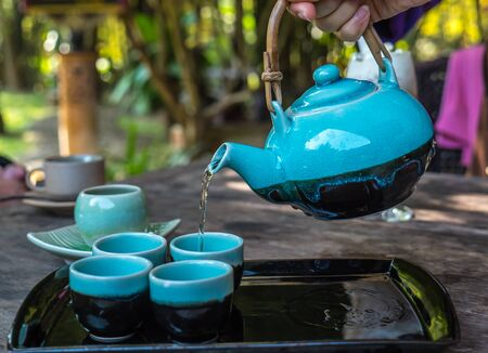 teakettle: Pour hot tea from teapot to  small cups