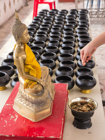 goodness: Put coin into small alms bowl, goodness belief in Buddhist religion
