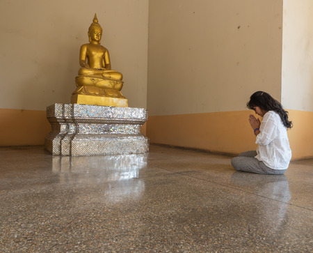 venerate: Thai woman pay homage to Buddha statue, Buddhist respect Stock Photo