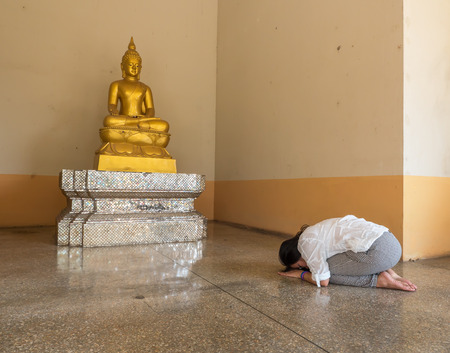 glorify: Thai woman pay homage to Buddha statue, Buddhist respect Stock Photo