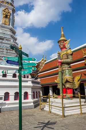 the grand palace: Giant statues in Temple of the Emerald Buddha or Grand palace and the guide post