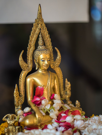 lei: Buddha statue with sacred lei flower Stock Photo