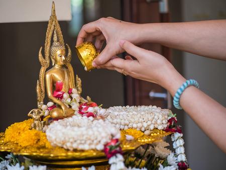 onto: Pour water onto a Buddha statue