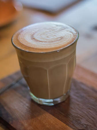 Cup of hot coffee on wooden board