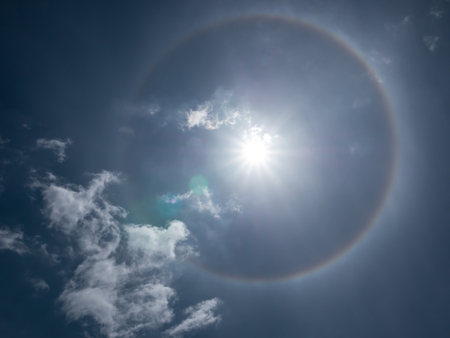Sun halo on blue sky background, natural phenomenon
