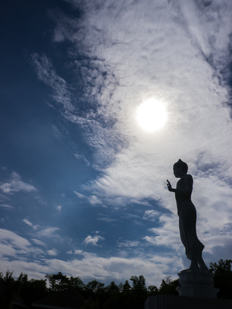 Buddha statue silhouette and sunray on blue sky background