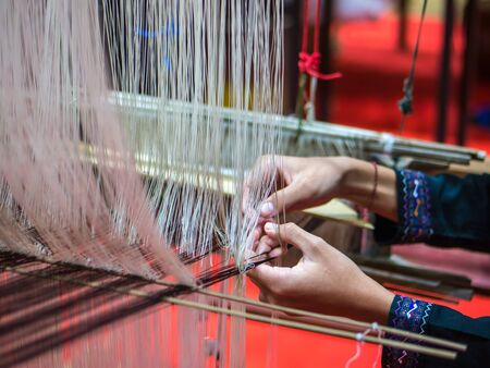 Local artist is weaving handicraft cloth with local apparatus