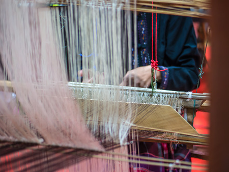 Thai artist is weaving handicraft cloth with local apparatus