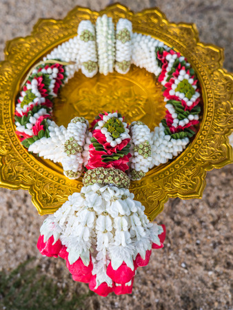Garland, lei of flowers on tray with pedestal for worship