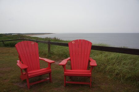 Red chairs inviting to East Coast of Canada 写真素材