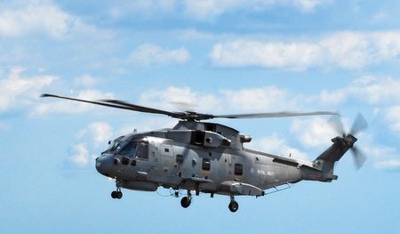 Merlin Military Helicopter flying right to left against a blue sky.
