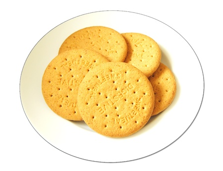 A white plate of five digestive biscuits isolated on a white background. Stock Photo
