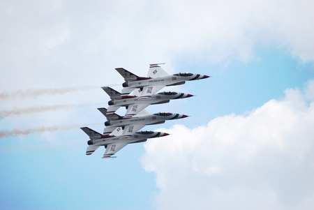 Four United States Airforce F16s flying in formation against a blue sky.
