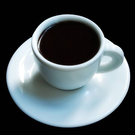 A tiny white cup of strong espresso coffee on a white saucer and all isolated on a black background. Stock Photo