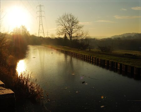A winter scene on the canal bank featuring late afternoon sun,sunbeams and an electricity pylon.Gritty unadorned canal scene.