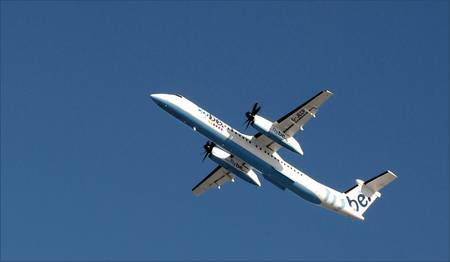 Twin engine propeller driven passenger plane against a clear blue february sky. Editorial