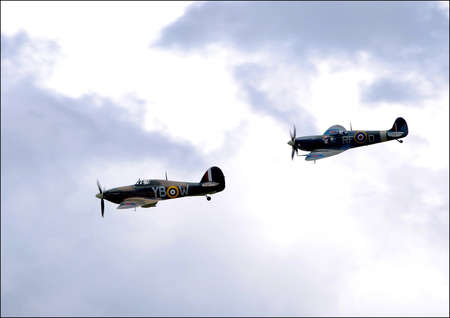 A Hawker Hurricane and Supermarine Spitfire in Loose Formation Chasing Across a Cloudy Sky